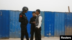 FILE - A police officer talks to men in a street in Kashgar, Xinjiang Uighur Autonomous Region, China, March 24, 2017.