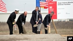 FILE - From left US Vice Admiral James D Syring, Romanian President Traian Basescu , US Undersecretary of Defense for Policy James N Miller, and Romanian Defense Minister Mircea Dusa shovel sand during the official ground breaking ceremony of an U.S. Aegis Ashore missile defense base in Deveselu, Romania, Oct. 28, 2013.
