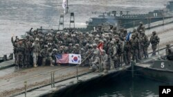 FILE - U.S. and South Korean army soldiers pose on a floating bridge on the Hantan river after a river crossing operation, part of an annual joint military exercise between South Korea and the United States in Yeoncheon, South Korea, Dec. 10, 2015.