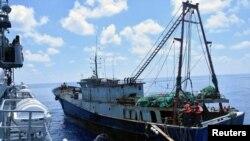 KRI Imam Bonjol (kiri) memeriksa kapal nelayan berbendera China, Han Tan Chou (kanan), di perairan dekat Kepulauan Natuna, 17 Juni 2016. (Foto: Reuters)