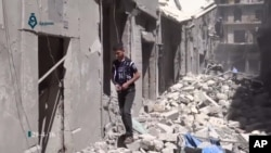 This image made from video released by Qasion News Agency, a media opposition platform that relies on a network of activists on the ground, on Friday, April 29, 2016 shows people scrambling through rubble following airstrikes in Aleppo, Syria.