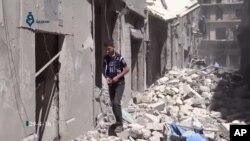 Warga bergegas melewati reruntuhan bangunan akibat serangan udara di Aleppo, Suriah (29/4).