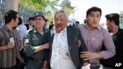 9일 폭탄 공격이 발생한 아프가니스탄 마자리 샤리프의 법원 앞에서 부상자가 부축을 받고 있다.