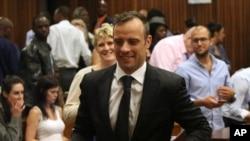 Oscar Pistorius (tengah) meninggalkan ruang pengadilan di Pretoria, Afrika Selatan, Selasa,(8/12).