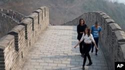 La primera dama de EE.UU., Michelle Obama, y sus hijas Malia y Sasha, caminan por la Gran Muralla China, este domingo, en Beijing.
