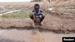 A man washes his hand with running water from a dug-out-trench in the drought stricken Somali region in Ethiopia, January 26, 2016.
