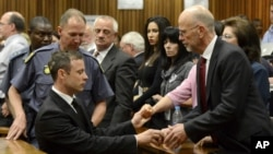 FILE - Oscar Pistorius, left front, greets his uncle Arnold Pistorius, right, and other family members as he is led out of court in Pretoria, South Africa, Oct. 21, 2014.