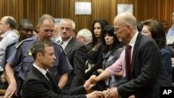 Oscar Pistorius, à gauche, salue son oncle Arnold Pistorius, à droite, et les autres membres de sa famille à Pretoria, en Afrique du Sud, le 21 octobre 2014.