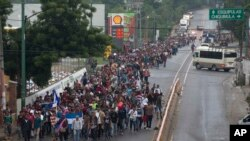 Honduran migrants walking to the U.S. start their day departing Chiquimula, Guatemala, Oct. 17, 2018. The group of more than 2,000 Honduran migrants hit the road in Guatemala again, hoping to reach the United States despite President Donald Trump's threat to cut off aid to Central American countries that don't stop them.