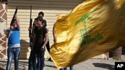 Hezbollah supporters fire weapons as they celebrate the fall of the Syrian town of Qusair to forces loyal to President Bashar Assad and Hezbollah fighters, in Bazzalieh village, Lebanon, near the Lebanese-Syrian border, June 5, 2013.