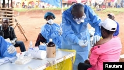 FILE - A Congolese health worker administers Ebola vaccine to a woman who had contact with an Ebola sufferer in the village of Mangina in North Kivu province of the Democratic Republic of Congo, Aug. 18, 2018.