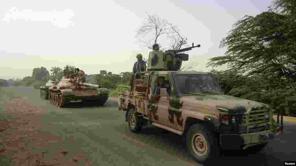 A military vehicle and tanks drive near the southern Yemeni city of Zinjibar after the army retook the city from al-Qaida-linked militants, June 12, 2012.