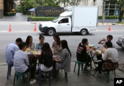 In this April 7, 2017 photo, people have their lunch at a street food shop on Thonglor road in Bangkok, Thailand. Officials see street food as an illegal nuisance and have warned hawkers in Thonglor to clear out by April 17.