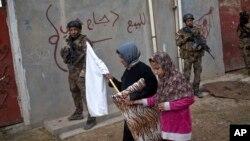 Civili sa belom zastavom prolaze pored pripadnika iračke specijalne jedinice u istočnom delu Mosula u Iraku, 2. novembar 2016.