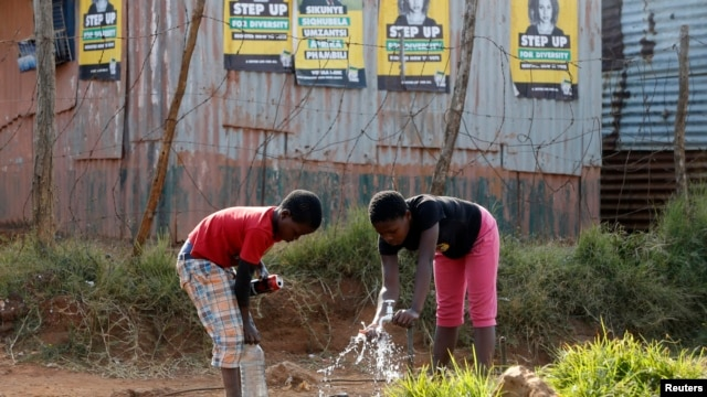 Children collect water from a communal tap beneath election posters for President Jacob Zuma's African National Congress (ANC) in Bekkersdal township south of Johannesburg, May 3, 2014.