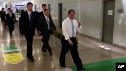 In this image made from video, Kim Yong Chol, in white, a former military intelligence chief who is now Kim Jong Un's top official on inter-Korean relations, walks upon arrival at Beijing airport in Beijing, May 29, 2018.