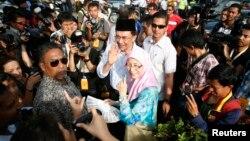 Pemimpin oposisi Malaysia Anwar Ibrahim dan istrinya Wan Azizah Wan Ismail meninggalkan TPS pasca memilih dalam pemilu nasional Malaysia di Permatang Pauh, Malaysia (5/5). Kepolisian Malaysia mengancam akan menangkap orang-orang yang ikut aksi demo tanpa izin untuk memprotes hasil pemilu.