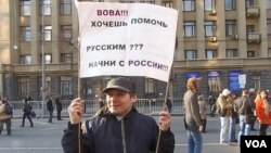 音乐家阿列克塞手举标语:普京你想帮助俄罗斯人吗?那就先从俄罗斯国内开始(美国之音白桦拍摄)