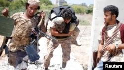 2016年7月31日,利比亚团结政府部队在苏尔特与伊斯兰国武装分子作战。政府军的一名战士掩护另外一名战士背着伤员撤离。