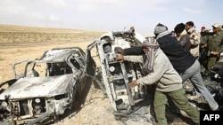 Chiến binh phe nổi dậy đẩy những chiếc xe bị cháy mà họ nói là du trúng đạn trong một cuộc không kích của liên quân trên xa lộ nối Ajdabiyah với Brega, Libya, ngày 2 tháng 4, 2011