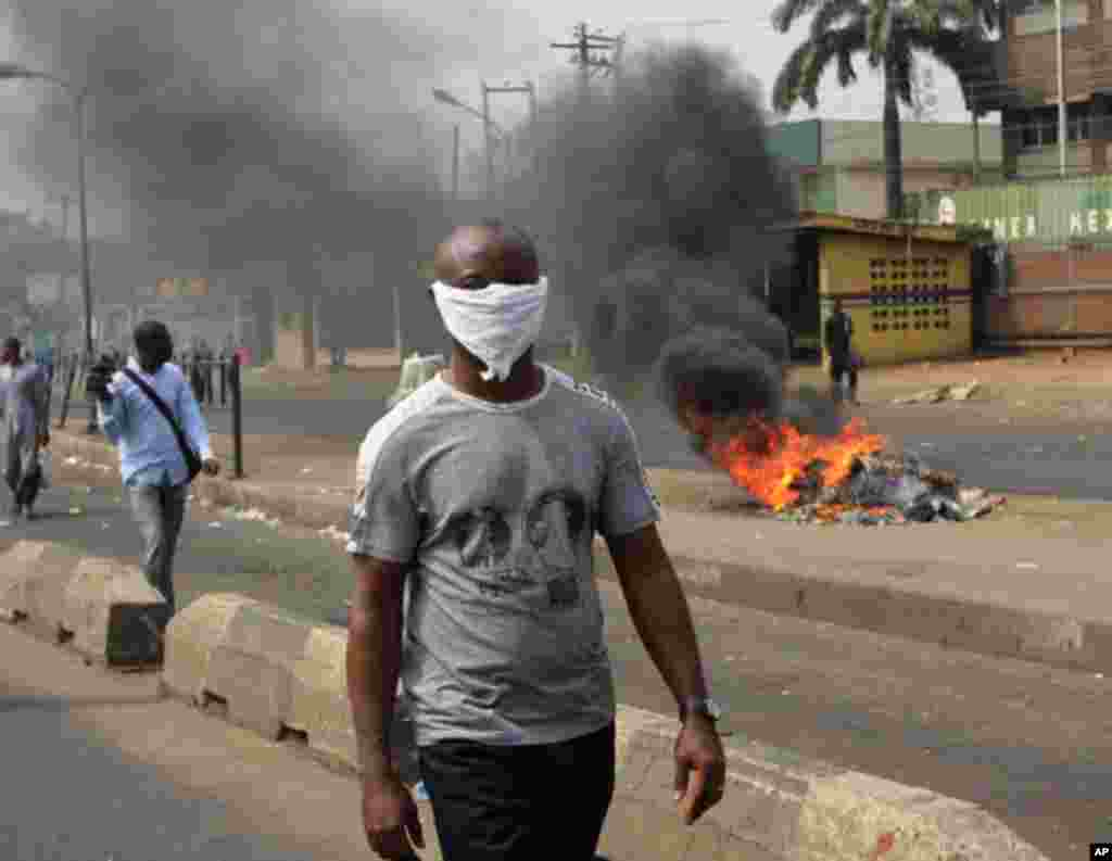 A man walk past a fire during a protest against the removal of fuel subsidy in Lagos ,Nigeria, on January 9, 2012. (AP)