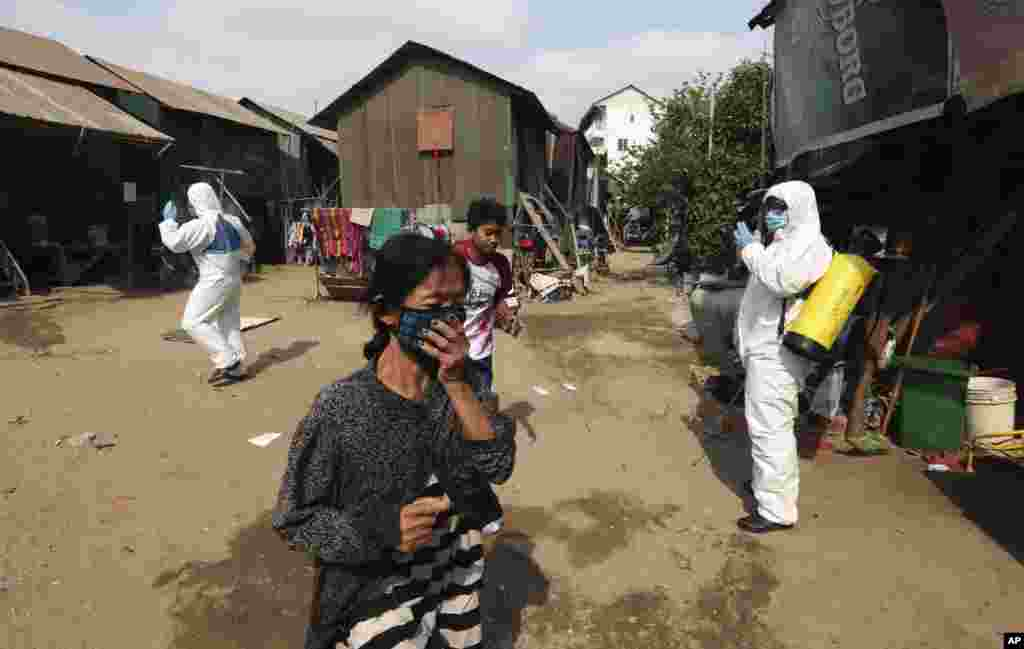 Villagers vacate the area as members of the non-profit Cambodian Children's Fund spray disinfectant to help curb the spread of the new coronavirus in the slum neighborhood of Stung Meanchey in southern Phnom Penh, Cambodia, on Tuesday, March 24, 2020. (AP Photo/Heng Sinith)