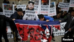 Protesters tear a defaced North Korean flag during an anti-North Korean rally in central Seoul, South Korea, Nov. 23, 2015. In the wake a group defection by 13 North Koreans, South Korea has warned its citizens of a hightned threat of abductions by
