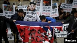 FILE - Protesters tear a defaced North Korean flag during an anti-North Korean rally in central Seoul, South Korea, Nov. 23, 2015. In the wake a group defection by 13 North Koreans, South Korea has warned its citizens of a hightned threat of abductions by