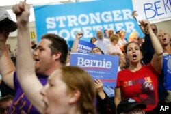 Supporters for Democratic presidential candidates Hillary Clinton and Sen. Bernie Sanders, I-Vt. cheer before a rally in Portsmouth, N.H., Tuesday, July 12, 2016