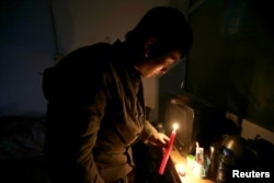 Migrant worker Chen Shuang lights a candle at an apartment where, according to manager of the building, security guards of the village cut off the power lines, at Xinjiancun, in Picun village on the outskirts of Beijing, China, Nov. 19, 2017.