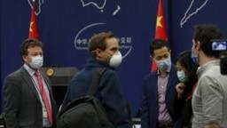 美���~约时�篑v北京�者史蒂文・李・�~��斯(左)在�⒓又��外交部例行�者��後�c其他外���者聊天。(2020年3月18日)