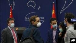 Корреспондент The New York Times в Пекине Стивен Ли Майерс (слева) беседует с другими иностранными журналистами во время пресс-брифинга во внешнеполитическом ведомстве КНР
