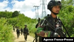 FILE - Military personnel arrive at Lembantongoa village in Palu, on Dec. 1, 2020, to track down Islamic State-linked extremists who killed four people in the remote Christian community on the Indonesian island of Sulawesi.