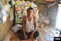 Ayub Khan, a displaced Rohingya man, sits in his family's UN shelter from where he sells medicine to residents in Baw Du Pha Camp 1 outside Sittwe. (P. Vrieze for VOA)