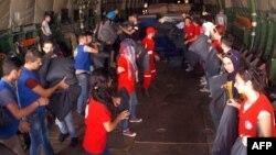 Các nhân viên tổ chức Trăng Lưỡi liềm đỏ của Syria chuyển hàng cứu trợ từ máy bay quân sự của Nga hôm 12/9.
