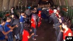 Foto yang diterbitkan oleh Kantor Berita Suriah Arab (SANA) para 12 September 2015 menunjukkan anggota Bulan Sabit Merah Suriah menurunkan bantuan kemanusiaan dari pesawat Rusia di bandara internasional Martyr Bassil al-Assad di Latakia.