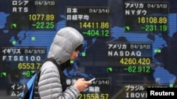 A man walks past an electronic board displaying various countries' stock price indices outside a brokerage in Tokyo, Japan, Mar. 14, 2014.