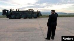 북한 김정은 국무위원장이 지난 9월 화성-12 발사 현장에서 발사 성공에 환호하는 북한군 지도부에 손을 흔들고 있다.