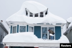 FILE - A man shovels snow from the roof of his home after a storm in Buffalo, N.Y., Nov. 20, 2014.