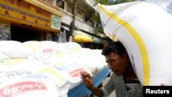 一名柬埔寨男子在金边的一辆卡车旁扛起一袋大米。(2017年7月12日)