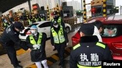 戴着面具的警察在武汉咸宁的高速缴费站检查汽车里是否载有偷运的野生动物。(2020年1月24日)