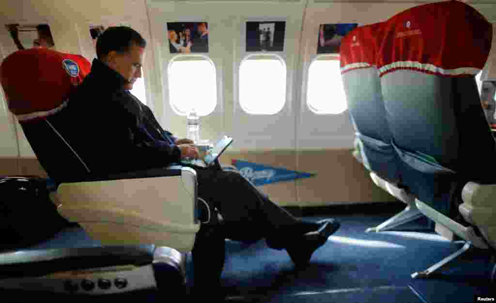 Mitt Romney looks at his iPad on his campaign plane en route to North Canton, Ohio October 26, 2012.
