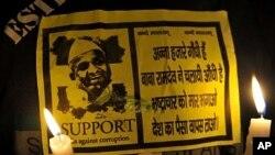 Một người ủng hộ nhà hoạt động xã hội Ấn Độ Anna Hazare thắp nến và cầm một tờ áp phích có hình ông Hazare tại một cuộc biểu tình phản đối ở New Delhi hôm 17/08/2011. (AFP)