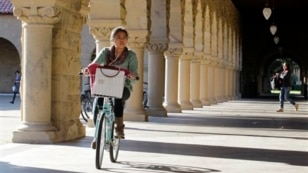 A Stanford University student bikes her way through the halls on the Stanford University campus in Palo Alto, Calif.