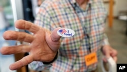 """FILE - Cliff Smith, a Ridgeland, Mississippi, poll worker, offers a voter an """"I Voted"""" sticker after they cast their ballot, Nov. 5, 2019."""
