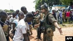 Des civils centrafricains discutent avec des militaires français de l'opération Sangaris à Bangui, 12 décembre 2013.