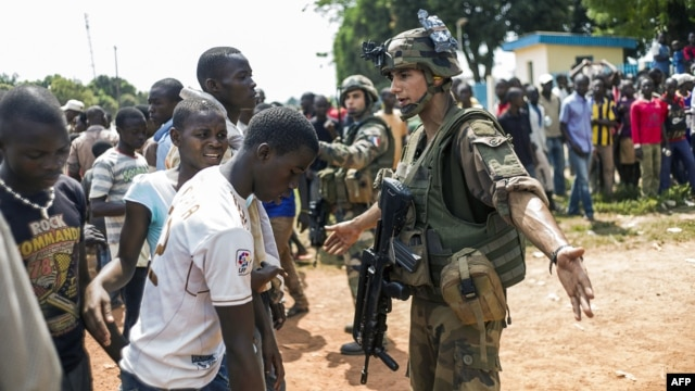 French troops of the Sangaris operation stop the crowds who have gathered at the entrance to the airport of Bangui, Central African Republic on Dec. 12, 2013.