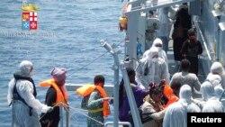 Para imigran menaiki kapal angkatan laut Italia Scirocco dalam operasi penyelamatan sekitar 40 mil dari laut Libya.