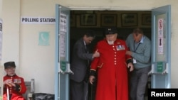 Chelsea Pensioner Wayne Campbell is helped out of a polling station after casting his vote in the general election, London, Britain, May 7, 2015. REUTERS/Paul Hackett - RTX1BXP5