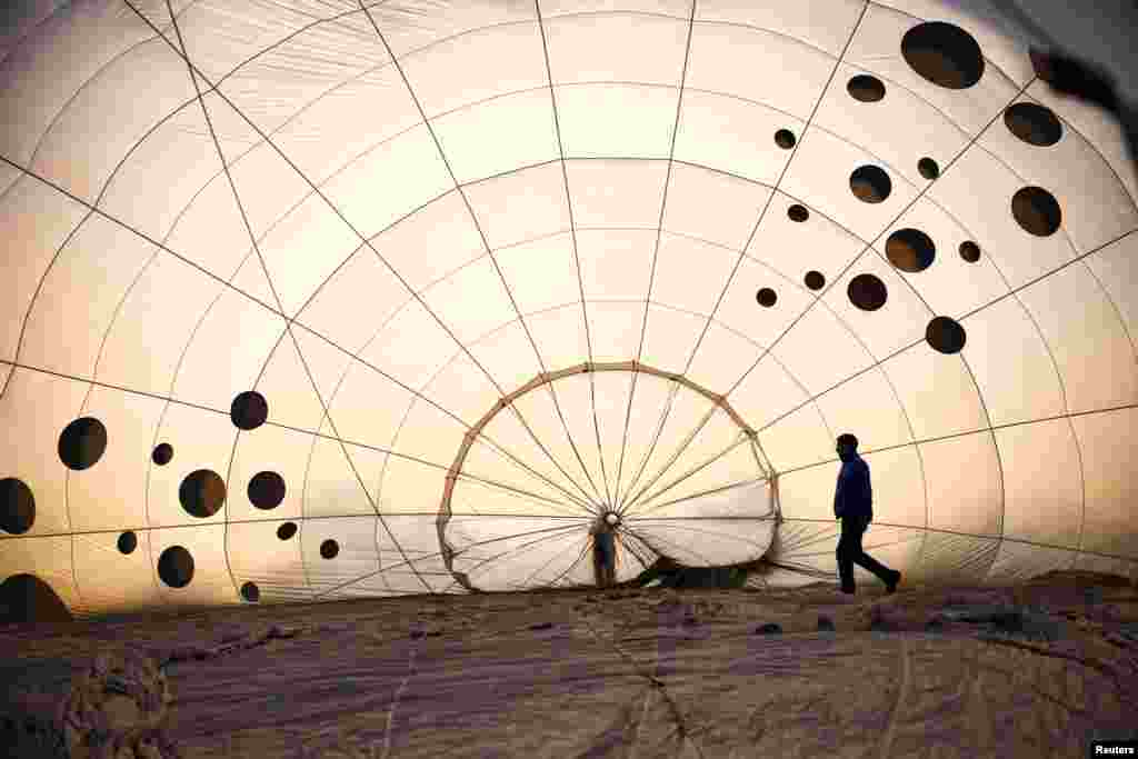 A crew member inspects a partially inflated hot air balloon at the Bristol International Balloon Fiesta in Bristol, Britain.